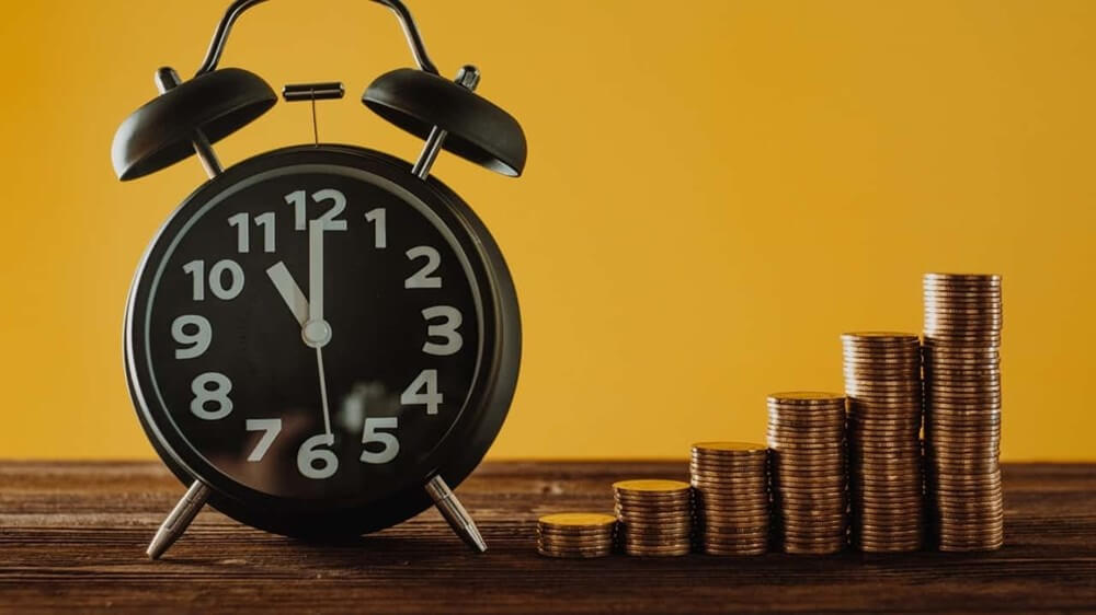 alarm clock and stacks of coins on a table
