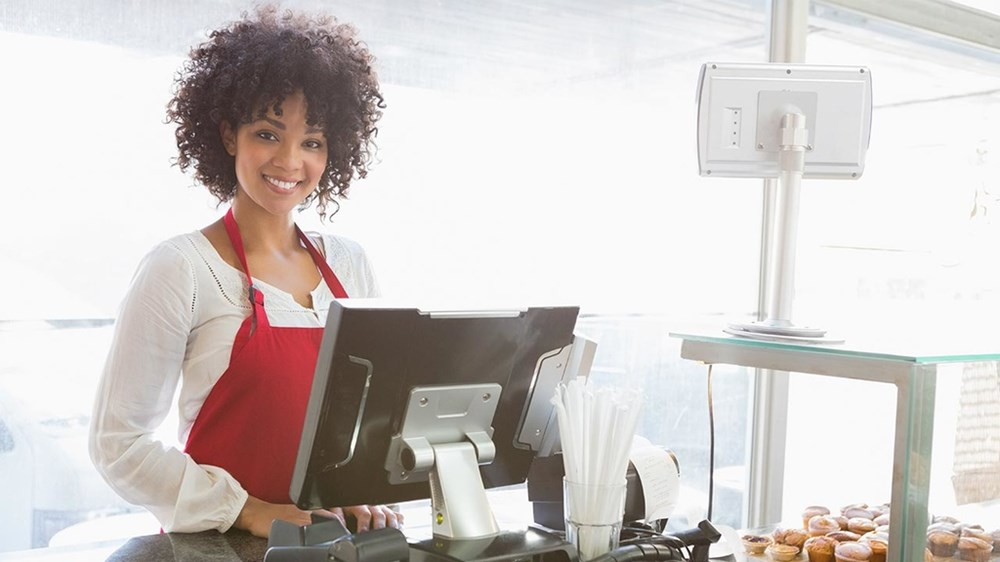 smiling woman with a red apron at a cash register