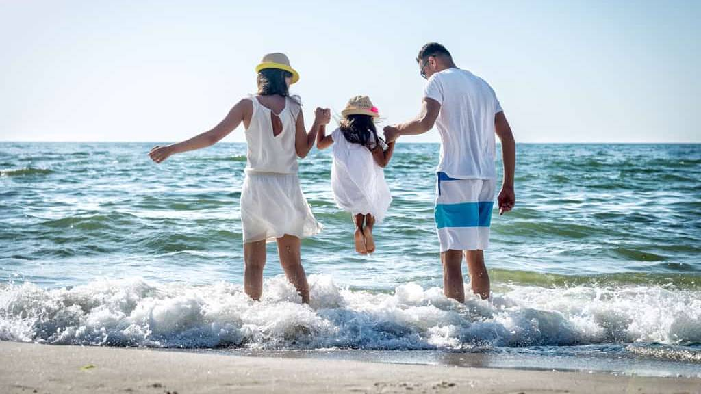 mother and father holding their daughter's hands as she jumps into ocean waves